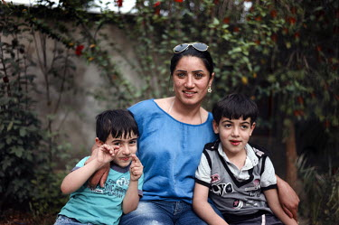 Fatima Bahmad, a deminer working for Mines Action Group (MAG), at home with her two sons Nasrala and Radwan.