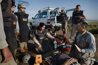 Deminers and medical staff, working for Mines Action Group's (MAG) Battle Area Clearance (BAC) team 3, administer first aid to the driver of an excavator as they wait for the medical team during a med...
