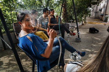 Fatima Bahmad, a deminer working for Mines Action Group (MAG), smokes a hookah (narghile, sheesha) with friends while off-duty.