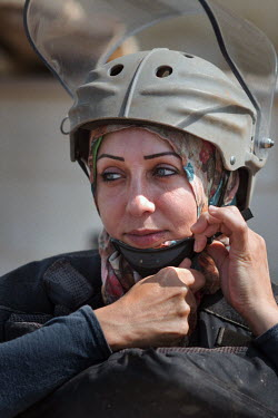 Amal Nader, a deminer working for Mines Action Group (MAG), adjusts the chin strap of her protective ballistic visor while working in the field.