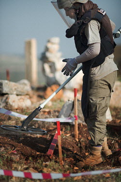 Layla Aboud, a deminer working for Mines Action Group (MAG), uses a metal detector while working with colleagues from Battle Area Clearance (BAC) team 3.