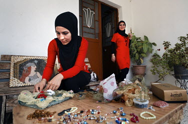 Layla Aboud, a deminer working for Mines Action Group (MAG), at home with her sister making a picture using beads, wire butterflies and textured fabric.
