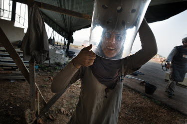 Layla Aboud, a deminer working for Mines Action Group (MAG), smiles as she looks through her protective ballistic visor to check it is clear after she had cleaned it.