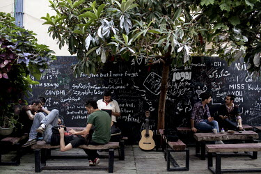 Yougn Kurdish people socialise at 'Eleven' cafe in Sulaymaniyah, with a guitar propped up against the wall.