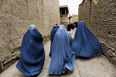 A group of women wearing flowing burqas walk through the streets of Kabul during Ashura. Ashura is observed by Shi'a (Shiite) Muslims at the end of a period of mourning for the martyrdom of Hussein ib...