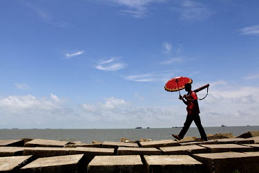A man carries a guitar in one hand and an umbrella, to shelter from the sun, in the other as he walks along a sea wall beside Patenga Beach, near Chittagong.