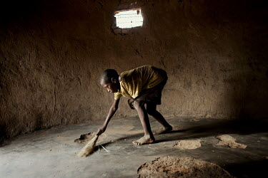 A child sweeps the floor of his mud built home. There are no adults in his household only children.