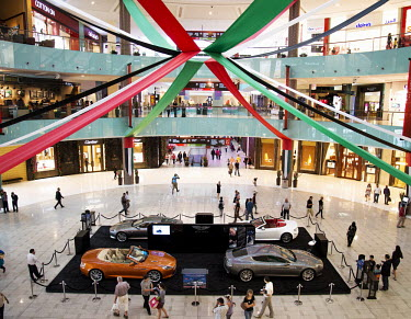 Shoppers walk around the Dubai Shopping Mall, one of the world's largest, with a set of four Aston Martin cars for sale in the middle of a large atrium.
