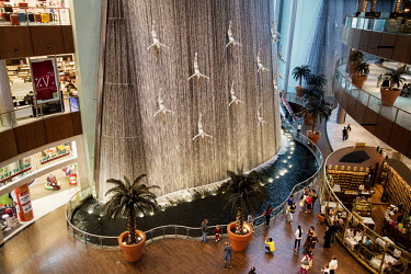 Shoppers stand next to a large indoor water feature with sculptures of divers descending from the ceiling inside the Dubai Shopping Mall, one of the world's largest.