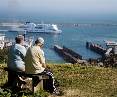 An elderly couple sit on a bench on a hill, watching the arrival of a MyFerryLink ferry into the port of Dover.