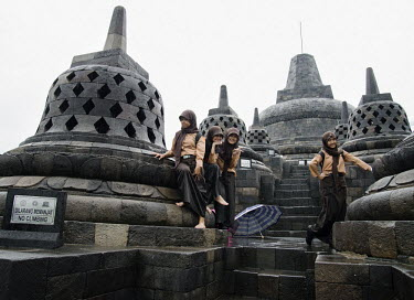 A group of school girls, in their uniforms, pose for a picture in the pouring rain while standing among the stupas at the 9th Century Mahayana Buddhist temple at Borobodur.