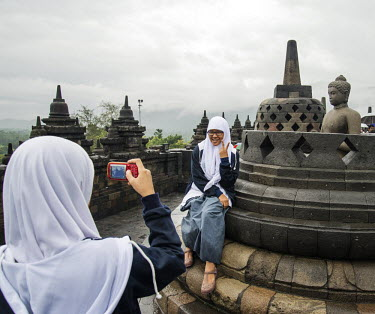 A pair of school girls, in their uniforms, pose for a picture at the 9th Century Mahayana Buddhist temple at Borobodur.