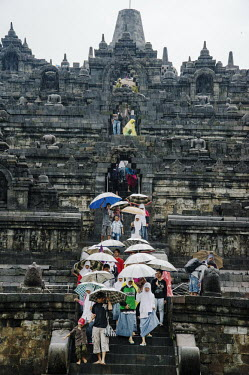 Tourists shelter from the pouring rain beneath umbrellas at the 9th Century Mahayana Buddhist temple at Borobodur.