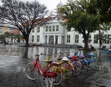 A row of colourful bicycles, availble for rent, lined up in front of the Jakarta History Museum, the former colonial era townhall.