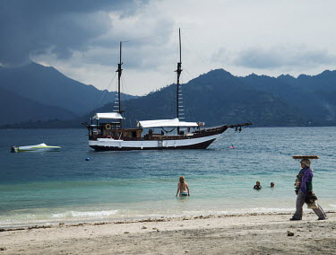 A beach hawker walks along the sand passing a sail boat and tourists swimming in the water.