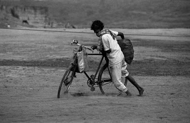 A man struggles through the sand with a bicycle loaded down by a sack of coal.