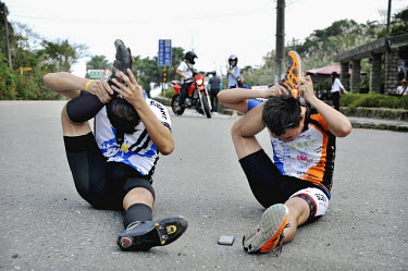 Cyclists stretch their legs to keep loose on their journey.