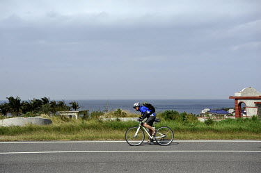 A cyclist passes a graveyard while riding the 'West Loop Route' near Kenting.