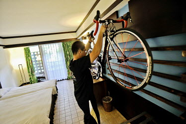 A guest in the cycle-friendly YOHO Bike Hotel stores his bike in his room.