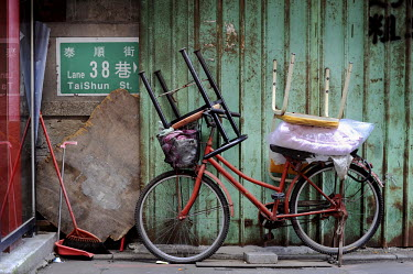 Chairs stacked on a bicycle next to a street sign in the city centre.