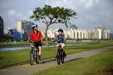 A man and a boy ride bicycles through the Dajia Riverside Park.
