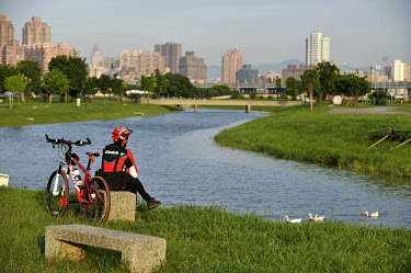 A rider takes a rest after riding a cycle route beside a tributary of the Taipei River, in the Sanchong district of Taipei.