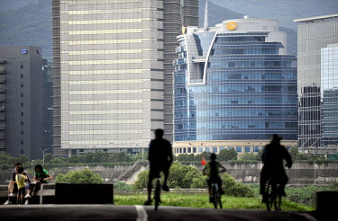 Cyclists on a riverside bicycle path in the Dajia Riverside Park, with the Neihu business district in the background.