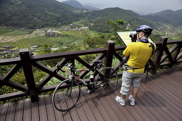 A cyclist photographs 'Bamboo Lake', an area of flower and vegetable cultivation on the side of the dormant Yangminshan Volcano.