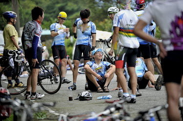 A group of avid cyclists rest at the top of a steep climb in Yangminshan National Park, a popular destination for cyclists.
