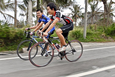 Riders cruise along a road on the east coast near to Taitung City.