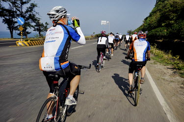 A group of cyclists riding on a circumnavigation of the island.