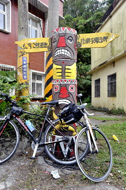 Bikes rest against a totem pole at the top of a popular hill climb on Route 199, just north of the Kenting National Park area.