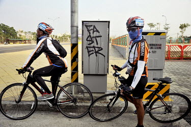 Two cyclists next to a grafitti that reads: 'faster' in Taichung City.