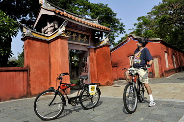 A tourist, riding a rented bike, stops outside a Confusion Temple.