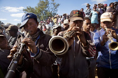 Three men, among a crowd, playing instruments during Famadihana, a funerary tradition of the Malagasy people. Known as the turning of the bones, people bring out the bodies of their ancestors from the...