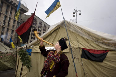 A young man from Ivano-Frankivsk Oblast in western Ukraine plays a horn in front of a tent in the tent city on Maidan Nezalezhnosti (Independent Square). Above the tent the Ukrainian national flag and...