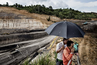 Surveyors measure and mark land for an expanding quarry at a mining concession in Indonesian Borneo. Land clearance for mining and palm oil plantations is wiping out Borneo's rainforests. More than ha...