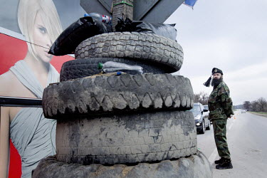 A militiaman wearing the insignia of Russian Cossacks on his fur cap mans a roadblock the town of Verkhn'osadove. The pro Russian militia have set up roadblocks to control movement around Crimea.   Si...