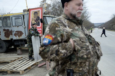 Pro Russian militia wearing the inisgnia of the Don Cossacks man a roadblock near Verkhn'osadove. They have set up roadblocks to control movement around Crimea.   Since the end of February, people in...