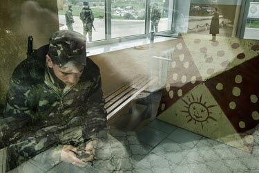 A soldier checks his phone while on guard duty at a military base at Belbek near Sevastopol. Following the fall of President Yanukovych in Kiev, militia wearing uniforms without insignia quickly moved...
