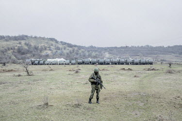A soldier wearing a uniform without insignia, presumed to be Russian or belonging to a pro Russian militia, stands guard at a Ukrainian military base in front of a row of army vehicles.   Following th...
