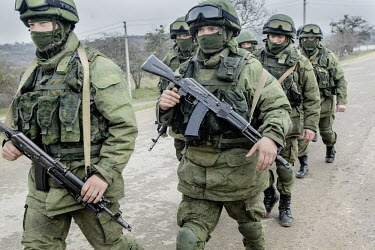 Soldiers wearing uniforms without insignia, presumed to be Russian or belonging to a pro Russian militia, march around a Ukrainian military base.  Following the fall of President Yanukovych in Kiev, m...