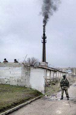 A soldier wearing a uniform without insignia, presumed to be Russian or belonging to a pro Russian militia, stands guard at a Ukrainian military base.  Following the fall of President Yanukovych in Ki...
