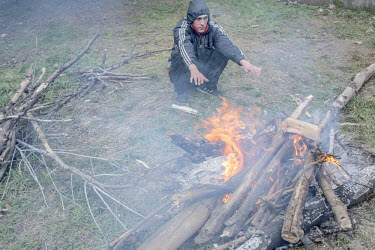 A pro Russian activist warms himself by the fire in a camp outside a military compound in Simferopol where people have gathered in support of Russian efforts in Crimea.   Following the fall of Preside...