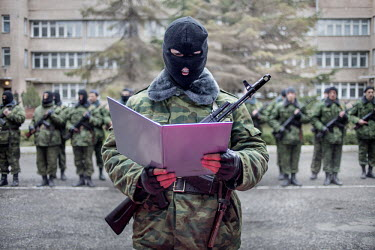 A man reads a declaration at a swearing in ceremony after they volunteered for a militia in support of the pro Russian administration of Crimea led by Sergey Aksyonov who was made Prime Minister of th...