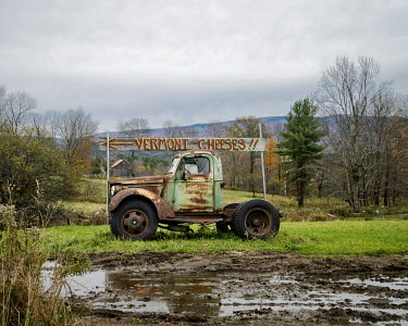 An old pickup truck supports a sign which points to a farm where they sell Vermont cheese. The state Vermont is famous for its cheeses.
