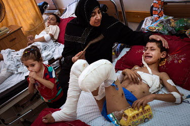 Ibrahim Kattab (6, right) and his brother, Wasim (15, left) recover in Shifa Hospital while watched over by their mother, Khetam (39) and their sister Nermine (3). Ibrahim is being fanned by his mothe...