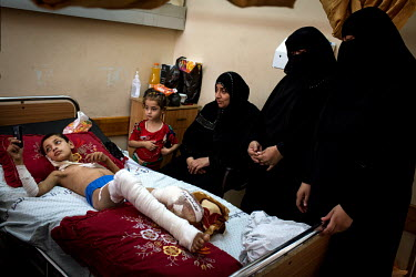 Ibrahim Kattab (6) pictured with members of his family by his beside as he recovers in Shifa Hospital, Gaza. Ibrahim and his brother, Wasim, were hit by shrapnel when a drone rocket hit his family's h...