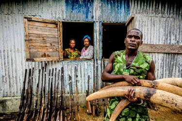 Mba Ndong Marius, part of the Gabonese army's newly formed section fighting wildlife crime, holds several seized ivory tusks while lined up behind him are a number of confiscated weapons.