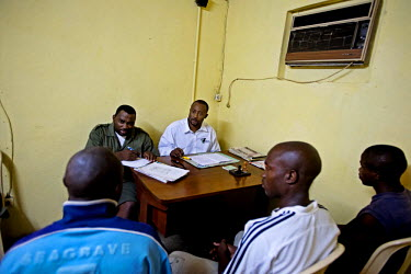 Convicted poachers are interrogated at a jail in Oyem by national parks officials. The two men on the right have been given three year jail sentences for killing elephants in addition to other crimes.
